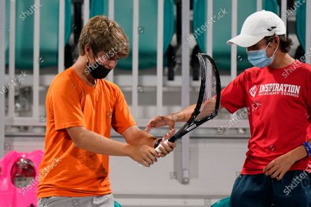 Two boys play with a smashed tennis racquet given to them by Dusan Lajovic, of Serbia, after his match with Frances Tiafoe during the Miami Open tennis tournament, early, in Miami Gardens, Fla