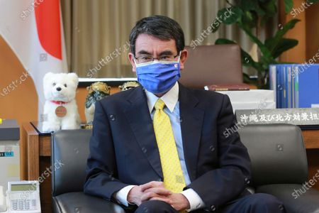 Japanese Vaccine Minister Taro Kono wearing a face mask with Japanese and EU flags on it speaks during an interview in Tokyo, . Kono tasked with COVID-19 vaccinations urged the EU to ensure stable shipment of Pfizer vaccines amid distribution uncertainty in a country where the Olympics are coming up in four months