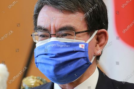 Japanese Vaccine Minister Taro Kono wearing a face mask with flags of Japan and EU, left, on it speaks during an interview in Tokyo, . Kono tasked with COVID-19 vaccinations urged the EU to ensure stable shipment of Pfizer vaccines amid distribution uncertainty in a country where the Olympics are coming up in four months