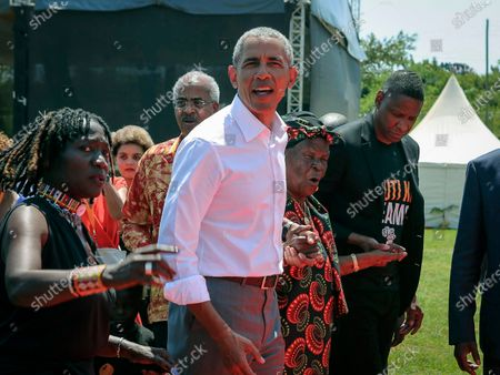 Then U.S. President Barack Obama, center, with his half sister Auma Obama, left, and his step-grandmother Sarah Obama, center-right, walk in Kogelo, western Kenya. Sarah Obama, the matriarch of Barack Obama's Kenyan family has died, relatives and officials confirmed Monday, March 29, 2021 but did not disclose the cause of death. She was at least 99 years old