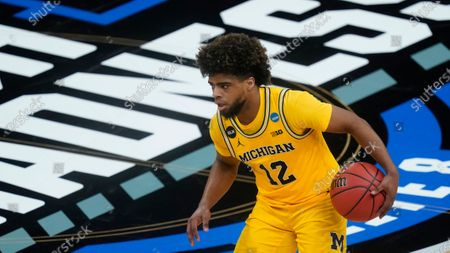Michigan's Mike Smith (12) dribbles during the second half of a Sweet 16 game in the NCAA men's college basketball tournament at Banker's Life Fieldhouse, in Indianapolis