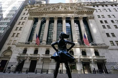The Fearless Girl statue stands in front of the New York Stock Exchange in New York's Financial District. On Monday, March 29, 2021, stocks are off to a mixed start on Wall Street as losses for banks are offset by gains in several Big Tech companies