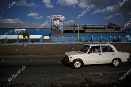 """Commuter drives a Soviet-era Lada car past a billboard of the late Fidel Castro with the words """"Socialism or Death"""" written on it in Havana, Cuba, . When the Ladas arrived in Cuba they were turned into taxis by the thousands and some went to government offices, the leaders of the Communist Party, and prominent workers"""