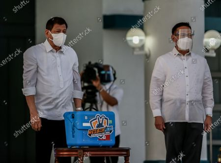 Stock Photo of (210329) - MANILA, March 29, 2021 (Xinhua) - Philippine President Rodrigo Duterte (L) stands beside Health Secretary Francisco Duque as they present a case containing government-purchased Sinovac COVID-19 vaccines in Manila, the Philippines, on March 29, 2021.   The Philippines on Monday received the first batch of the Sinovac COVID-19 vaccines it government has purchased from China.