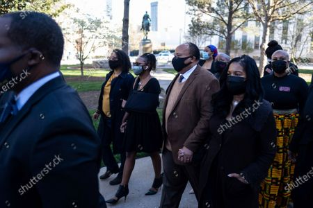 Georgia State Rep. Park Cannon, D-Atlanta, center with arm in sling, walks beside Martin Luther King, III, as she returns to the State Capitol in Atlanta on Monday morning, after being arrested last week for knocking on the governor's office door as he signed voting legislation