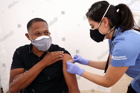 Brenda Rojas places a band-aide on Tony Brown, left, after he received his vaccine against the coronavirus at Kedren Community Health Center Inc. with a new initiative to expand vaccines to underserved communities in South LA on Friday, March 26, 2021 in Los Angeles, CA. (Dania Maxwell / Los Angeles Times)