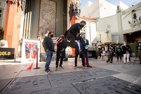 Adam Wingard jumps after cutting the red ribbon during the post-pandemic reopening and ribbon cutting ceremony hosted by TCL Chinese Theatre in Hollywood, California, USA, 29 March 2021.