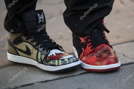 Stock Image of Jordan Vogt-Roberts and Adam Wingard wear a pair of snickers designed in relation to the Godzilla vs. Kong movie during the post-pandemic reopening and ribbon cutting ceremony hosted by TCL Chinese Theatre in Hollywood, California, USA, 29 March 2021.