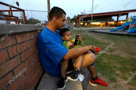 """Stock Photo of MISSION, TEXAS - MISSION, TEXAS - March 23, 2021-Migrant Guillermo Alejandro Valle, holds his son Jonathan, age 2, at a shelter in Mission, Texas. Valle said that he and his family spent three days shivering under the bridge for three days with his sons - 11 month-old Axel and 2 year-old Jonathan - felt like part of the price. Cold and dirty, he didn't sleep. """"This is how we suffer to get here,"""" Valle said after being released Tuesday to a local shelter, where he washed and changed into donated clothes.  March 23, 2021 in Mission, Texas. (Carolyn Cole / Los Angeles Times)"""