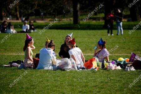 A group of six young women wearing party hats picnic in warm spring sunshine in Hyde Park in London, England, on March 29, 2021. Lockdown restrictions were eased across England today, with the 'stay home' rule ended, groups of up to six allowed to meet outside, outdoor sports restarted and weddings with up to six people attending permitted to go ahead. Shops, hospitality and leisure businesses remain closed however, with the next relaxation of restrictions not due until April 12 at the earliest. Today's easing has meanwhile coincided with the first of a three-day 'mini-heatwave', with daytime temperatures in London forecast to rise above 20C until the latter half of this week.