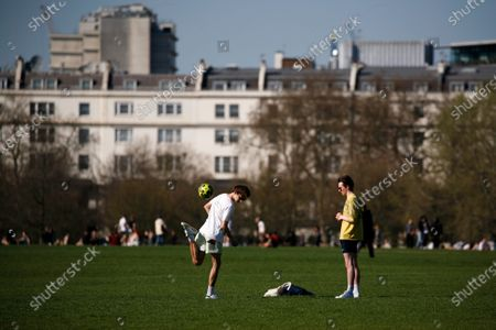 A pair of young men play with a football in warm spring sunshine in Hyde Park in London, England, on March 29, 2021. Lockdown restrictions were eased across England today, with the 'stay home' rule ended, groups of up to six allowed to meet outside, outdoor sports restarted and weddings with up to six people attending permitted to go ahead. Shops, hospitality and leisure businesses remain closed however, with the next relaxation of restrictions not due until April 12 at the earliest. Today's easing has meanwhile coincided with the first of a three-day 'mini-heatwave', with daytime temperatures in London forecast to rise above 20C until the latter half of this week.