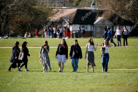 A group of young women walk through warm spring sunshine in Hyde Park in London, England, on March 29, 2021. Lockdown restrictions were eased across England today, with the 'stay home' rule ended, groups of up to six allowed to meet outside, outdoor sports restarted and weddings with up to six people attending permitted to go ahead. Shops, hospitality and leisure businesses remain closed however, with the next relaxation of restrictions not due until April 12 at the earliest. Today's easing has meanwhile coincided with the first of a three-day 'mini-heatwave', with daytime temperatures in London forecast to rise above 20C until the latter half of this week.