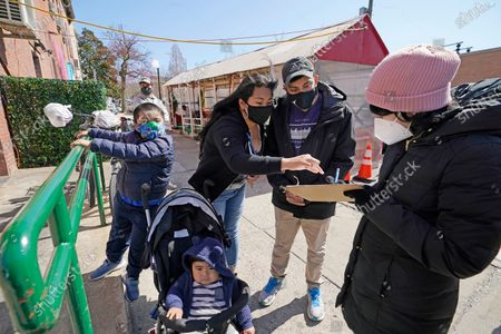 Stock Photo of Elizabeth Reyes, center, helps husband Max, second from right, register for a COVID-19 vaccination with Mixteca volunteer and first responder Areli Prado, right, as the Reyes' children Irvin, 5, and Ivan, 10 months, stand nearby during a visit to a mobile vaccination van in the Sunset Park neighborhood of Brooklyn, in New York. Reyes also booked an appointment for her mother. The family is especially vigilant after Reye's father died of coronavirus about a year ago. NYC Test & Trace Corps added mobile vaccination to its community vaccine clinic program Monday, launching a clinic-on-wheels with Mixteca, a community-based organization serving New York City's Spanish and indigenous-speaking Latin American community