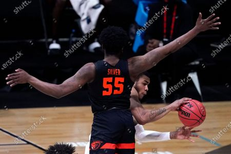 Houston forward Reggie Chaney passes around Oregon State guard Tariq Silver (55) during the first half of an Elite 8 game in the NCAA men's college basketball tournament at Lucas Oil Stadium, in Indianapolis