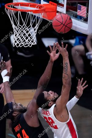 Houston forward Reggie Chaney (32) shoots ahead of Oregon State forward Rodrigue Andela, left, during the first half of an Elite 8 game in the NCAA men's college basketball tournament at Lucas Oil Stadium, in Indianapolis