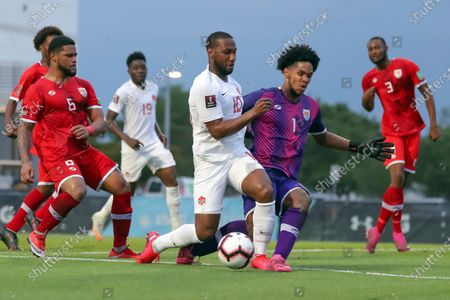 Stock Photo of Canada's David Hoilett (10) collides with Cayman Islands goalkeeper Albertini Holness as Wesley Robinson (6) and Ackeem Hyde (3) defend during the second half of a World Cup 2022 Group B qualifying soccer match, in Bradenton, Fla