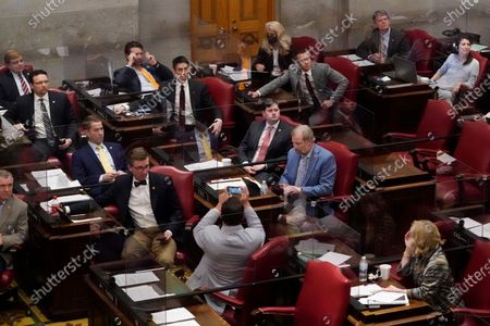 Members of the Tennessee House of Representatives cast their votes and watch the tally board as they vote on a bill allowing most adults to carry handguns without obtaining a permit, in Nashville, Tenn. The bill passed the House, 64-29, and can now be signed into law by Gov. Bill Lee