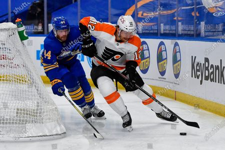 Philadelphia Flyers left wing Michael Raffl (12) shields the puck from Buffalo Sabres defenseman Matt Irwin (44) during the first period of an NHL hockey game in Buffalo, N.Y