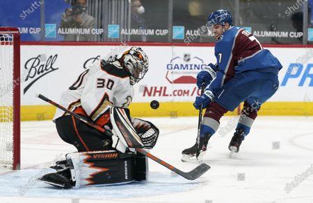 Anaheim Ducks goaltender Ryan Miller, left, stops a shot by Colorado Avalanche defenseman Devon Toews in the first period of an NHL hockey game, in Denver