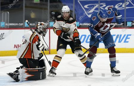 Colorado Avalanche right wing Joonas Donskoi, right, tries to redirect the puck past Anaheim Ducks defenseman Ben Hutton, center, and goaltender Ryan Miller in the first period of an NHL hockey game, in Denver