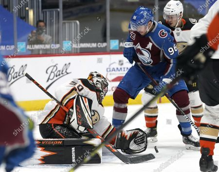 Anaheim Ducks goaltender Ryan Miller, left, makes a glove save of a redirected puck off the stick of Colorado Avalanche right wing Mikko Rantanen in the first period of an NHL hockey game, in Denver