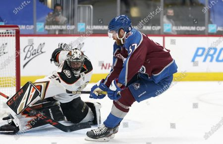 Anaheim Ducks goaltender Ryan Miller, left, deflects a breakaway shot by Colorado Avalanche left wing J.T. Compher in the first period of an NHL hockey game, in Denver