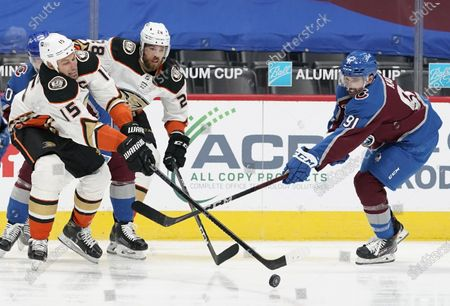 Anaheim Ducks center Ryan Getzlaf, left, reaches out to control the puck as Colorado Avalanche center Nazem Kadri defends and Ducks center Derek Grant, back, follows the play in the second period of an NHL hockey game, in Denver