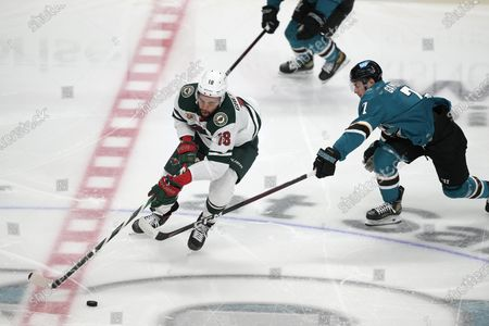Minnesota Wild left wing Jordan Greenway (18) battles for the puck against San Jose Sharks center Dylan Gambrell (7) during the first period of an NHL hockey game in San Jose, Calif