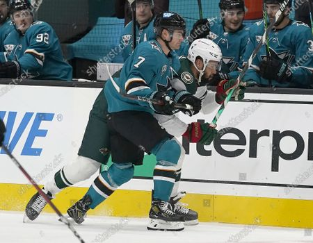 Minnesota Wild left wing Jordan Greenway (18) is checked into the boards by San Jose Sharks center Dylan Gambrell (7) during the second period of an NHL hockey game in San Jose, Calif