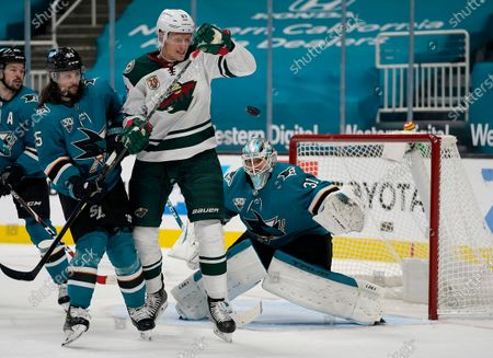 Minnesota Wild center Nick Bjugstad (27) moves out of the way on a shot at San Jose Sharks goaltender Martin Jones (31) as defenseman Erik Karlsson (65) defends during the second period of an NHL hockey game in San Jose, Calif