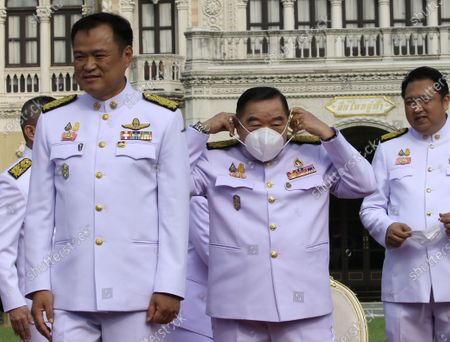 Thai Deputy Prime Minister General Prawit Wongsuwan (C) wears a face mask next the Public Health Minister Anutin Charnvirakul (L) and the Labour Minister Suchart Chomklin (R) during a group photo after a cabinet reshuffle, at Government House in Bangkok, Thailand, 30 March 2021. The new Thai government named three new ministers to replace vacant positions. The reshuffle comes in the wake of a 24 February court ruling that convicted former Education Minister Nataphol Teepsuwan, Digital Economy and Society Minister Buddhipongse Punnakanta and Deputy Transport Minister Thaworn Senneam guilty of protesting against the government of former Prime Minister Yingluck Shinawatra in 2013-14. The new Thai government will face increasing political tension as the anti-government and pro-democracy movement holds protests across Thailand. Chan-o-cha is the leader of the military junta which has governed Thailand since 22 May 2014.