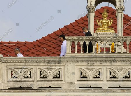 Stock Image of The newly appointed Deputy Minister of Commerce Sinit Lertkrai (L) and the newly Education Minister Treenuch Thienthong (C) walk on the top of a building after paying respect to the Brahma shrine, before a group photo after a cabinet reshuffle, at Government House in Bangkok, Thailand, 30 March 2021. The new Thai government named three new ministers to replace vacant positions. The reshuffle comes in the wake of a 24 February court ruling that convicted former Education Minister Nataphol Teepsuwan, Digital Economy and Society Minister Buddhipongse Punnakanta and Deputy Transport Minister Thaworn Senneam guilty of protesting against the government of former Prime Minister Yingluck Shinawatra in 2013-14. The new Thai government will face increasing political tension as the anti-government and pro-democracy movement holds protests across Thailand. Chan-o-cha is the leader of the military junta which has governed Thailand since 22 May 2014.