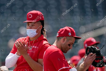 Stock Picture of Cincinnati Reds' Luis Castillo, left, and Joey Votto applaud U.S. veterans as they are recognized at Goodyear Ballpark during the second inning of a spring training baseball game against the Seattle Mariners, in Goodyear, Ariz