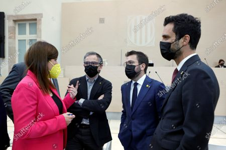 Stock Photo of ERC's candidate for Catalonia's regional Presidency, Pere Aragones (2-R), chats with party colleagues Roger Torrent (R) and Josep MAria Jove (3-R) and JxCat MP Gemma Geis (L) at the Catalan Parliament in Barcelona, Spain, 30 March 2021, before a second vote on Aragones' investiture after the first one failed the previous week.