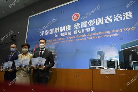 Stock Image of From Left to Right Mr. Eric Tsang   Secretary for Constitutional and Mainland Affairs , Ms Carrie Lam Hong Kong Chief Executive , Mr Roy Tang Permanent Secretary for Constitutional and Mainland Affairs, holds a booklet while posing for a photo before a press conference in Hong Kong, Tuesday, March 30, 2020. The National People's Congress Standing Committee (NPCSC) on Tuesday approved amendments to annexes 1 and 2 of Hong Kong's Basic Law to pave the way for a drastic overhaul of the SAR's electoral system, local member Tam Yiu-chung said One of the major revamps includes expanding the role of the election committee that currently chooses Hong Kong's leader so that it will, in future, also participate in the nomination of all Legco candidates and pick some members of the council itself. There will also be changes to the size, composition and method for forming the election committee.