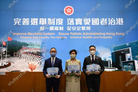 From Left to Right Mr. Eric Tsang   Secretary for Constitutional and Mainland Affairs , Ms Carrie Lam Hong Kong Chief Executive , Mr Roy Tang Permanent Secretary for Constitutional and Mainland Affairs, holds a booklet while posing for a photo before a press conference in Hong Kong, Tuesday, March 30, 2020. The National People's Congress Standing Committee (NPCSC) on Tuesday approved amendments to annexes 1 and 2 of Hong Kong's Basic Law to pave the way for a drastic overhaul of the SAR's electoral system, local member Tam Yiu-chung said One of the major revamps includes expanding the role of the election committee that currently chooses Hong Kong's leader so that it will, in future, also participate in the nomination of all Legco candidates and pick some members of the council itself. There will also be changes to the size, composition and method for forming the election committee.