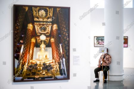 A guard holds a sign advising visitors to wear their protective face mask at all times at the  'Life @ Home' Royal photo exhibition at the BACC (Bangkok Arts and Culture Center) in Bangkok, Thailand, 30 March 2021. The Royal exhibit showcases photographs taken by Thai Princess Maha Chakri Sirindhorn, mostly focusing on daily life, nature and animals. The exhibition runs until 18 April 2021.
