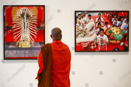 Stock Picture of A Thai Buddhist monk visits the 'Life @ Home' Royal photo exhibition at the BACC (Bangkok Arts and Culture Center) in Bangkok, Thailand, 30 March 2021. The Royal exhibit showcases photographs taken by Thai Princess Maha Chakri Sirindhorn, mostly focusing on daily life, nature and animals. The exhibition runs until 18 April 2021.