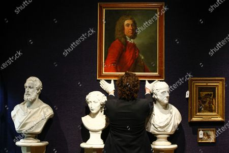 A member of staff poses holding an oil on canvas portrait of General James Grant of Ballindalloch (1720-1806), attributed to Allan Ramsay, estimated at GBP7,000-10,000, and between three of a collection of six Victorian plaster busts, estimated at GBP-1,200-1,800, during a press preview for the upcoming sale of items from Scotland's Dunrobin Castle, under instruction from the 25th Earl of Sutherland, at Bonhams auction house in London, England, on March 30, 2021. The sale itself takes place on April 20 in Edinburgh.