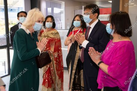Britain's Camilla The Duchess, front left, meets with directors of Kamsons Pharmacy Bharat Chotai and Bipin Chotai, left, and family members during a visit to Kamsons Pharmacy head office and warehouse, in East Sussex, England, . The Duchess of Cornwall is visiting to thank frontline coronavirus workers