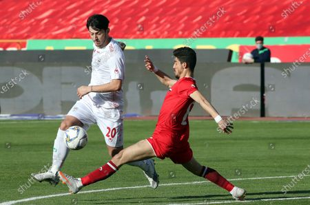 Iran's Sardar Azmoun (L) in action against Syria's Kamel Hmeisheh (R) during the International friendly soccer match between Iran and Syria at the Azadi stadium in Tehran, Iran, 30 March 2021.