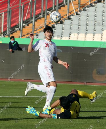 Iran's Sardar Azmoun (L) in action against Syria's goalkeeper Alma Ibrahim during the International friendly soccer match between Iran and Syria at the Azadi stadium in Tehran, Iran, 30 March 2021.