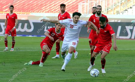 Iran's Sardar Azmoun (C) in action against Syria's Youssef Al Hamwi (R) during the International Friendly soccer match between Iran and Syria at the Azadi stadium in Tehran, Iran, 30 March 2021.