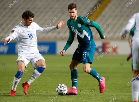 Cyprus' Kostakis Artymatas, left, and Slovenia's Kenan Bajric challenge for the ball during the World Cup 2022 group H qualifying soccer match between Cyprus and Slovenia at GSP stadium in Nicosia, Cyprus