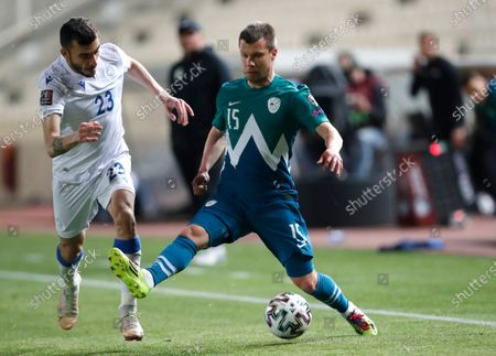 Cyprus' Ioannis Pittas, left, and Slovenia's Damjan Bohar challenge for the ball during the World Cup 2022 group H qualifying soccer match between Cyprus and Slovenia at GSP stadium in Nicosia, Cyprus
