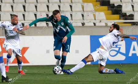 Cyprus' Fotis Papoulis, left, Cyprus' Paris Psaltis, right, and Slovenia's Josip Ilicic challenge for the ball during the World Cup 2022 group H qualifying soccer match between Cyprus and Slovenia at GSP stadium in Nicosia, Cyprus