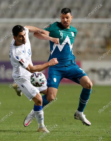 Cyprus' Ioannis Kousoulos, left, and Slovenia's Haris Vuckic challenge for the ball during the World Cup 2022 group H qualifying soccer match between Cyprus and Slovenia at GSP stadium in Nicosia, Cyprus