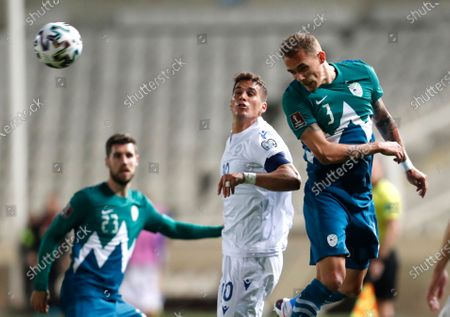 Slovenia's Jure Balkovec, right, heads the ball during the World Cup 2022 group H qualifying soccer match between Cyprus and Slovenia at GSP stadium in Nicosia, Cyprus