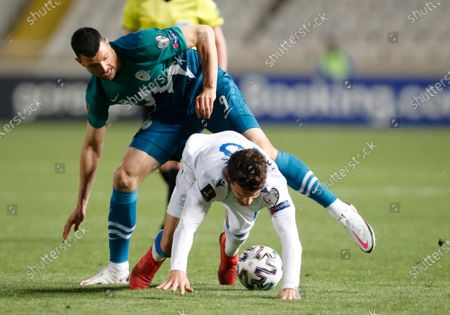 Slovenia's Haris Vuckic, left, and Cyprus' Kostakis Artymatas challenge for the ball during the World Cup 2022 group H qualifying soccer match between Cyprus and Slovenia at GSP stadium in Nicosia, Cyprus