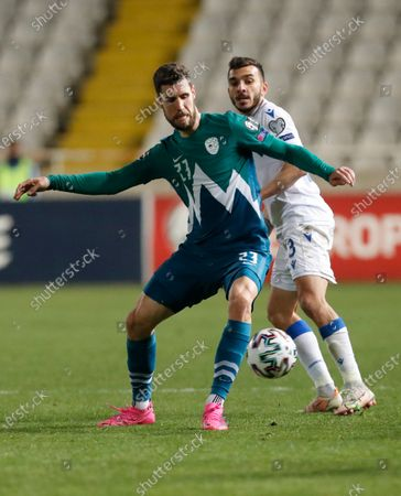Slovenia's Kenan Bajric, left, and Cyprus' Ioannis Pittas challenge for the ball during the World Cup 2022 group H qualifying soccer match between Cyprus and Slovenia at GSP stadium in Nicosia, Cyprus